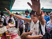 31 AUGUST 2014 - SARIKA, NAKHON NAYOK, THAILAND: A Thai woman prays at the Ganesh festival at Shri Utthayan Ganesha Temple in Sarika, Nakhon Nayok. Ganesh Chaturthi, also known as Vinayaka Chaturthi, is a Hindu festival dedicated to Lord Ganesh. It is a 10-day festival marking the birthday of Ganesh, who is widely worshiped for his auspicious beginnings. Ganesh is the patron of arts and sciences, the deity of intellect and wisdom -- identified by his elephant head. The holiday is celebrated for 10 days, in 2014, most Hindu temples will submerge their Ganesh shrines and deities on September 7. Wat Utthaya Ganesh in Nakhon Nayok province, is a Buddhist temple that venerates Ganesh, who is popular with Thai Buddhists. The temple draws both Buddhists and Hindus and celebrates the Ganesh holiday a week ahead of most other places.    PHOTO BY JACK KURTZ