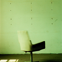 An empty room with an office chair and sunlight