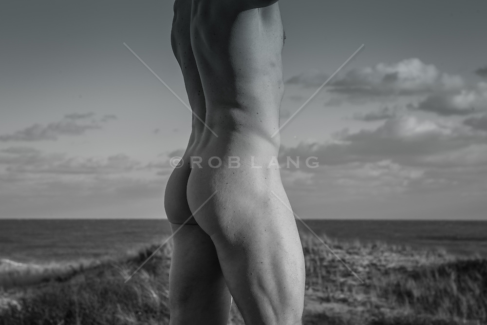 Detail of a muscular nude man's ass outdoors by the beach