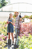 Portrait of happy gardeners standing outside greenhouse