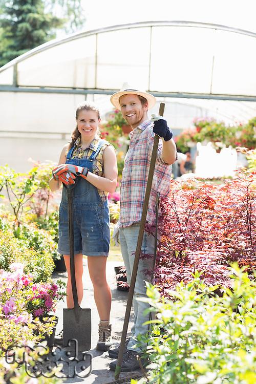 Portrait of happy gardeners standing outside greenhouse
