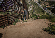 Encounter with unidentified man, likely a &ldquo;coyote&rdquo; human trafficker, talking on a telephone while carefully studying a vulnerable stretch of the US-built border wall in Tijuana.  There is a gap in the second, stronger wall on the US side, offering an opportunity to traffickers of people and drugs about 1 &frac12; miles from the Pacific Ocean.  On the US side, there is a state park parking area, which could serve as a rendezvous to traffickers&rsquo; partners on the US side of this heavily-surveilled stretch of the border.<br /> <br /> In order to document deportees who live atop this hilltop, it was necessary to climb the steep slope from the highway below, entering territory controlled by &ldquo;coyotes&rdquo; who work for Mexican cartels that control the flow of people and drugs across the border.  <br /> <br /> This man is attempting to obscure his identity and subsequently confronted me because I had a camera.  I was able to calm him by mentioning, by name, one of the deportees I had met for the first time two days before on this hilltop.  The deportees showed me a safer route down so that I could avoid this route when I descended to the highway again.