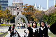 School girls have their photo taken in front of the Peace Memorial and, in the distance, the A-Bomb Dome in Hiroshima, Japan.