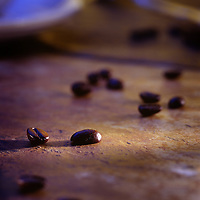 coffee beans spilled on counter by cup of coffee in the morning light.