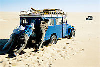 Men pushing jeep in desert