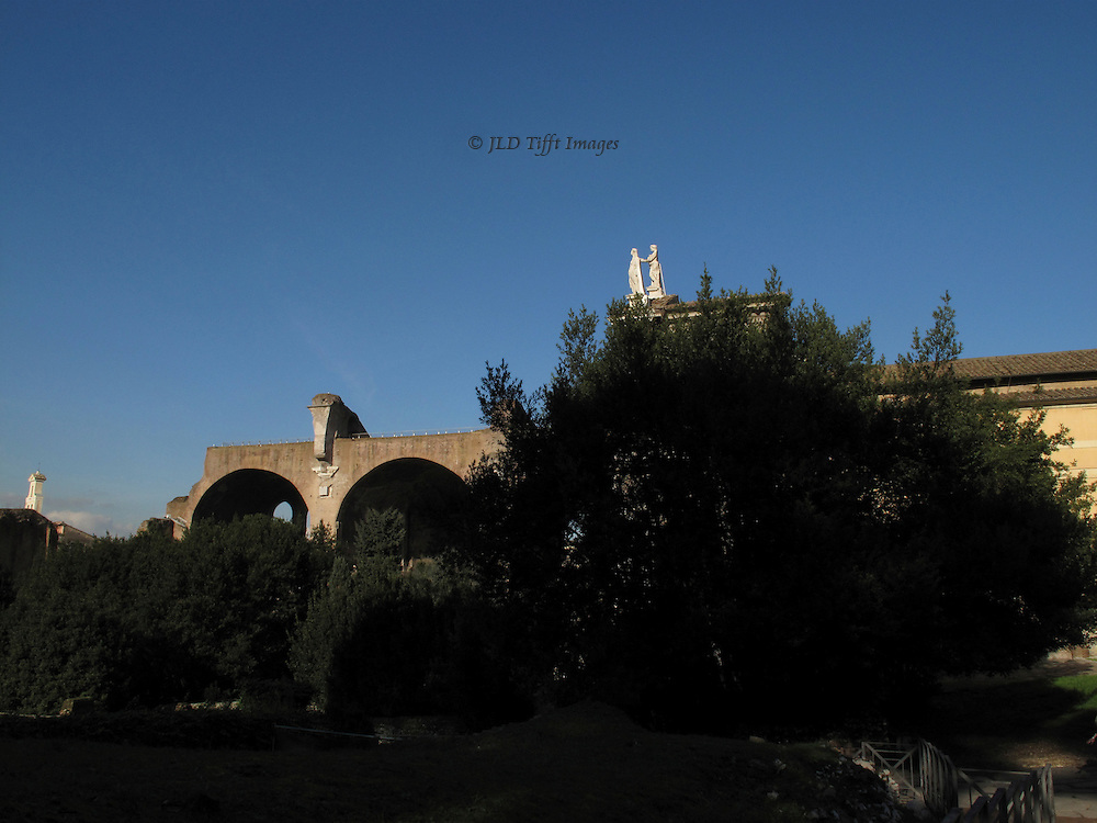 Roman Forum, Basilica of Constantine, seen beyond a grove of trees near the Arch of Titus, above which a pair of statues on top of Santa Francesca Romana's travertine façade (by Carlo Lambardi, 1615) seem to be floating on top of the tree branches.  Clear plain blue sky above.