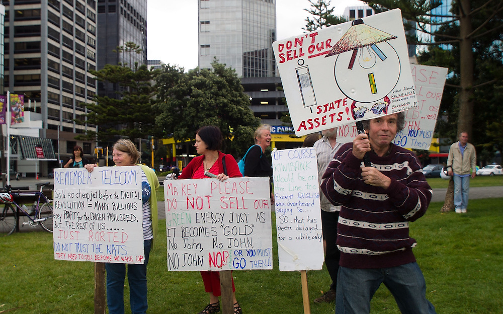 Protesters hold placards during a rally against asset sales at Frank Kitts Park, Wellington, New Zealand, Wednesday, February 13, 2013. Credit: SNPA / Marty Melville