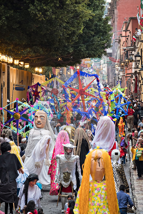 Giant paper mache puppets in a fiesta procession through the city at the start of the week long fiesta of the patron saint Saint Michael September 22, 2017 in San Miguel de Allende, Mexico.