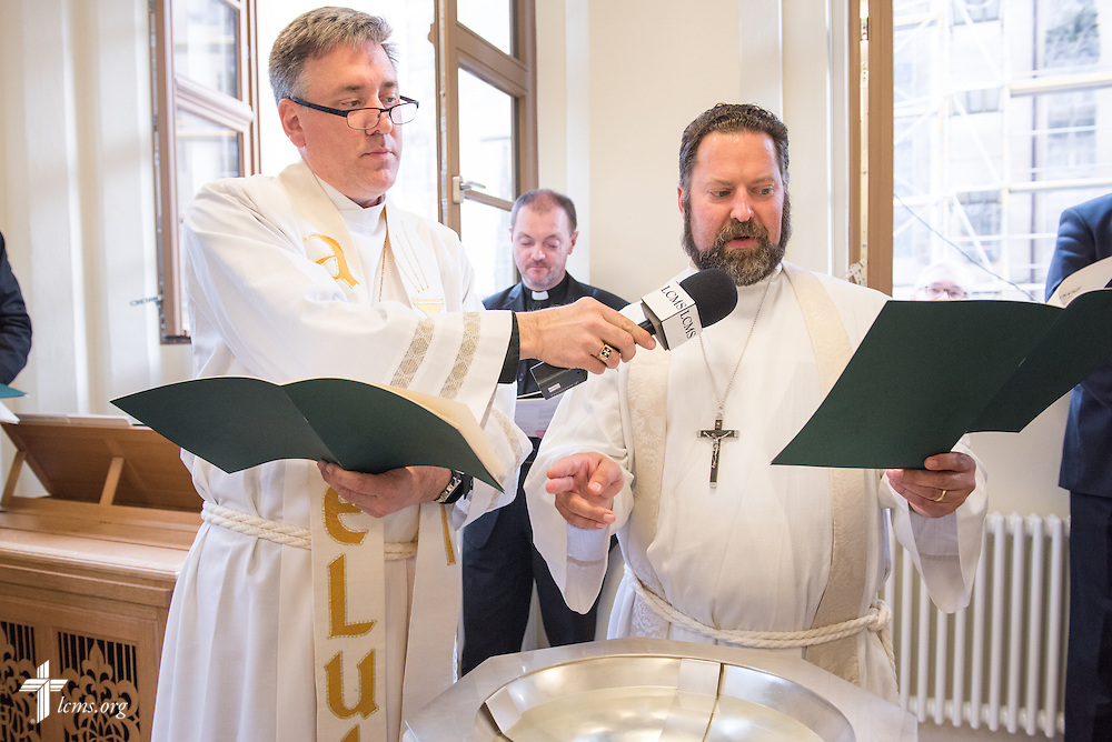 The Rev. Dr. Albert C. Collver, director of Church Relations and Regional Operations for the LCMS, blesses the baptismal font with the help of the Rev. Dr. Jon D. Vieker,  senior assistant to Rev. Dr. Matthew C. Harrison, president of The Lutheran Church–Missouri Synod, during the dedication of The International Lutheran Center at the Old Latin School on Sunday, May 3, 2015, in Wittenberg, Germany.  LCMS Communications/Erik M. Lunsford