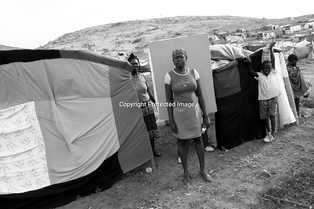 "Guerda Jean, 40, came to the Canaan II tent camp to live after the earthquake made her homeless and killed her sister. She was reduced to tears, fleeing into the street and holding her children tight. ""Jesus save me!"" She remembers crying out. With red thread, she sewed a tent for her family from old clothes and blankets. ""We have no tarps, so it's very troubling. We do what we can here. We share."""