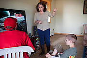 Talon Shannon, 15, (left) and Drake Shannon, 11, (right) two of the three children of John Daniel Shannon, 48, a former US Army Senior Sniper, are being reprimanded by their mother, Torrey Shannon, 42, (centre) for playing for too much time on their X-Box, inside the family home in Westcliffe, CO, USA. Daniel retired here with his family after a serious brain injury inflicted by an insurgent sniper in Ramadi, Al Anbar Province, Iraq, on November 13th 2004. He fought during the Second Battle of Fallujah and was then moved to nearby Ramadi. Daniel lost his left eye and has multiple health issues because of his injury: memory problems, balance problems, he can't smell and taste well anymore, he suffers from PTSD, has  troubles with large crowds and city surroundings. This is the reason why he and his family moved to a quiet location on the Rocky Mountains. In 2007 Dan helped the Washington Post to uncover patients' neglect at the Walter Reed Army Medical Center; he also testified before Congress. Torrey, 42, his wife, is a freelance writer and a contributor for the Huffington Post; she's also campaigning to improve the situation of veterans' families.