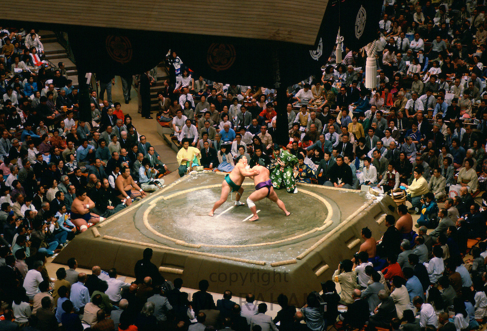 Sumo wrestlers in the ring watched by a big crowd  in Tokyo, Japan
