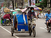 24 JANUARY 2018 - LIGAO, ALBAY, PHILIPPINES: A pedicab driver wearing a breathing filter during a volcanic ash fall in Ligao. The Mayon volcano continued to erupt Tuesday night and Wednesday forcing the Albay provincial government to order more evacuations. By Wednesday evening (Philippine time) more than 60,000 people had been evacuated from communities around the volcano to shelters outside of the 8 kilometer danger zone. Additionally, ash falls continued to disrupt life beyond the danger zones. Several airports in the region, including the airport in Legazpi, the busiest airport in the region, are closed indefinitely because of the amount of ash the volcano has thrown into the air.    PHOTO BY JACK KURTZ