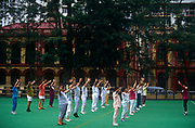 With colonial Portuguese architecture in the background, older women and a few men participate in a group exercise on an astroturf-covered sports ground, on 10th August 1994, in Macau, China. The Macau Special Administrative Region is one of the two special administrative regions of the People's Republic of China (PRC), along with Hong Kong. Administered by Portugal until 1999, it was the oldest European colony in China, dating back to the 16th century. The administrative power over Macau was transferred to the People's Republic of China (PRC) in 1999, 2 years after Hong Kong's own handover.