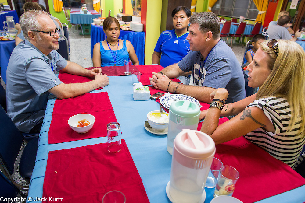 "02 APRIL 2013 - PATTAYA, CHONBURI, THAILAND: Scott Bessenecker, left, Saiyuud ""Poo"" Diwong, her husband, Khun Kare, Ash Barker and his wife Anji Barker chat after dinner at the Ray Resort, in Pattaya, Thailand.     PHOTO BY JACK KURTZ"