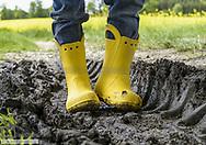 Kleiner Junge mit gelben Gummistiefeln steht in Reifenspur, Nahaufnahme (model-released)