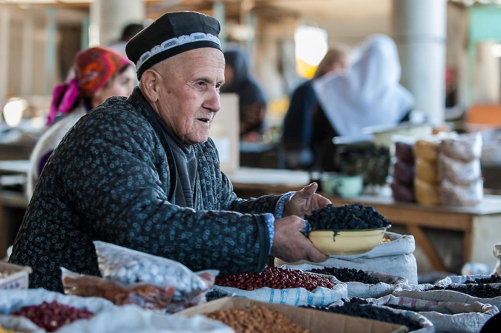 Portrait of an old Tajik man selling raisins and beans in a market in western Tajikistan
