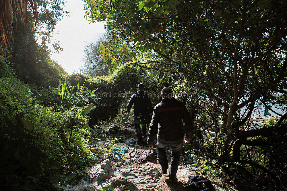 VENTIMIGLIA, ITALY - 20 NOVEMBER 2014: Syrian refugees enter a trail near the Italian-French border  in Ventimiglia, Italy, on November 20th 2014. They had first tried to cross the border by train in the morning, but were caught by the French police that pushed them back to the Italian border.<br /> <br /> The Ventimiglia-Menton border is the border between Italy and France crossed by migrants who decide to continue their journey up north towards countries such as Germany, Sweden, The Netherlands and the UK where the process to receive the refugee status or humanitarian protection is smoother and faster. in Ventimiglia, Italy, on November 17th 2014.