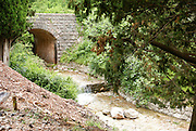 small stream flows under a stone bridge, near Becici, Budva Riviera, Montenegro