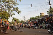 Bundi, India - A cyclist in the town market rides below a monkey crossing a wire.  In this part of India, people who rely on the bicycle as a tool for daily transportation are increasingly replacing them with inexpensive motorcycles.