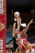 05.07.2011 Paula Griffin of New Zealand(black) plays the ball over the outstretched hands of Jamilla Abbott during the Pool B match between New Zealand and Wales, Mission Foods World Netball Championships 2011 from the Singapore Indoor Stadium in Singapore.