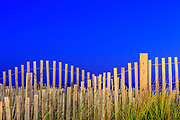 Sand fence at Kitty Hawk Pier photographed at twilight using the incandescent walkway lights to light the fence.