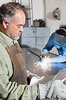 Mature man reading paper while young male welding in background