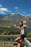 Two women taking picture against a fence in countryside with mountains behind