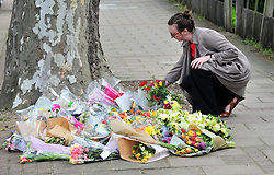© Licensed to London News Pictures.23/04/2018<br /> ELTHAM, UK.<br /> A lady laying flowers this morning.<br /> Stephen Lawrence memorial plaque in Well Hall Road, Eltham is covered in floral tributes on the 25th anniversary of his murder.<br /> Photo credit: Grant Falvey/LNP