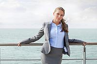 Portrait of confident businesswoman leaning on terrace railings