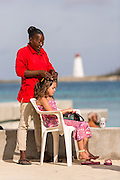 A bahamian woman braids a young tourists hair along Junkanoo Beach in Nassau, Bahamas