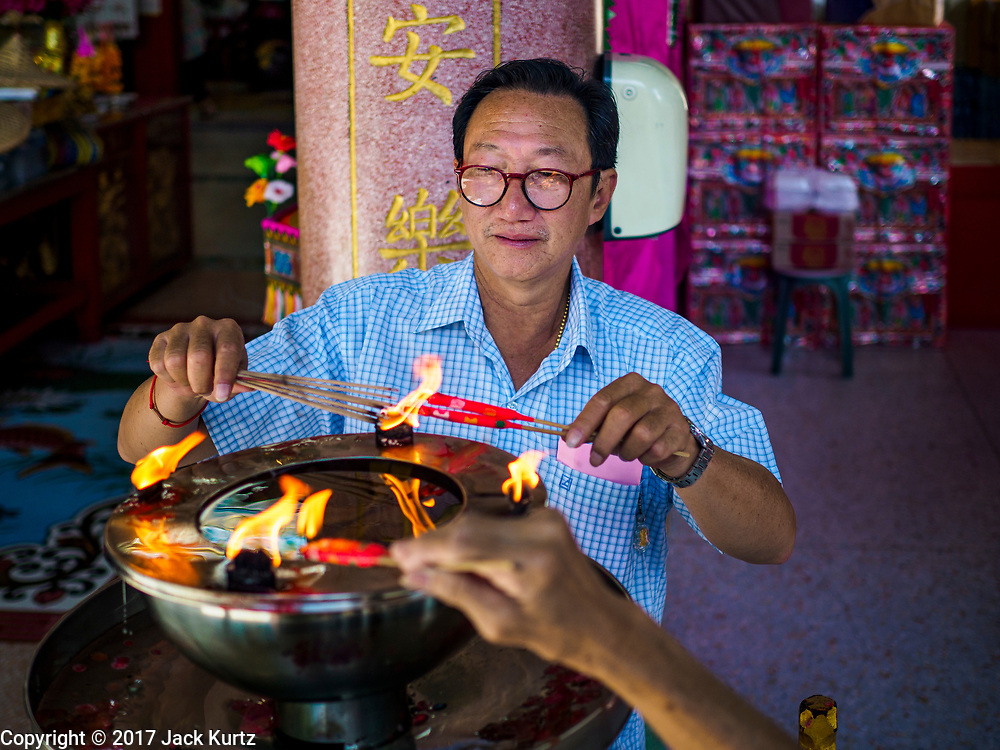 "22 AUGUST 2017 - BANGKOK, THAILAND: A man lights incense and prayer candles before praying on the first day of Hungry Ghost Month at the Poh Teck Tung Shrine in Bangkok's Chinatown. The seventh lunar month (August - September) is when many Chinese believe Hell's gate will open to allow spirits to roam freely in the human world. Many households and temples hold prayer ceremonies throughout the month-long Hungry Ghost Festival (Phor Thor) to appease the spirits. During the festival, believers will also worship the Tai Su Yeah (King of Hades) in the form of paper effigies which will be ""sent back"" to hell after the effigies are burnt.      PHOTO BY JACK KURTZ"