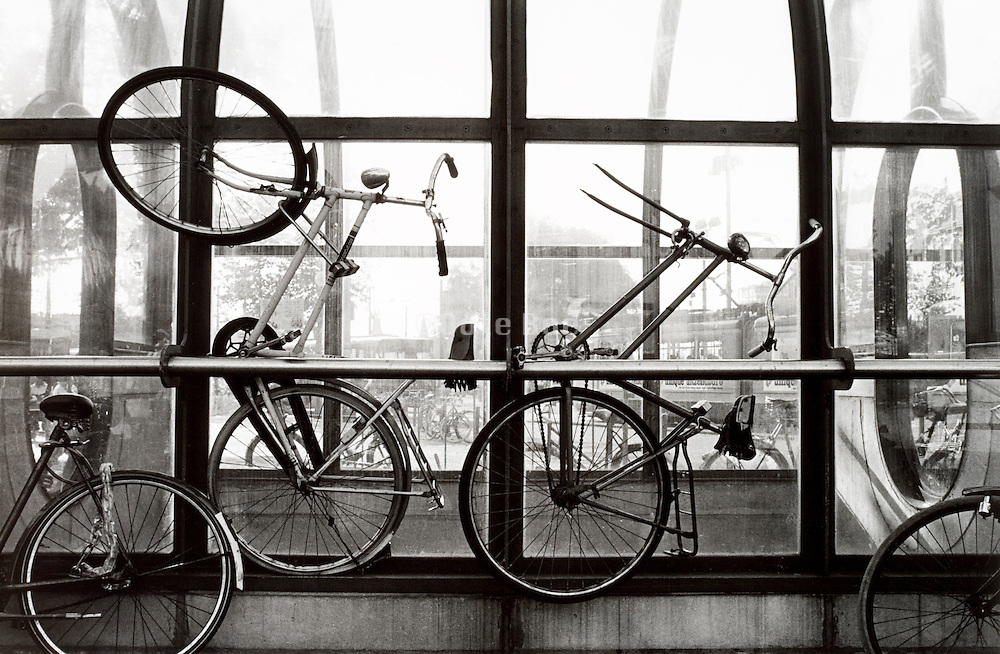 Bicycles against railing with city in background, Amsterdam, Central Station, Holland