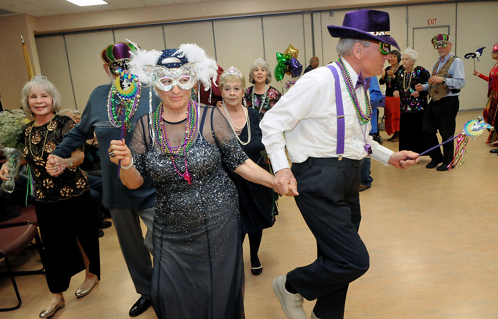 jt030217c/a sec/jim thompson/ Michael Twining takes hold of the hand of Clara Urioste and heads towards the dance floor at the Mardi Gras celebration at the Meadowlark Senior Center.  Thursday March 02, 2017. (Jim Thompson/Albuquerque Journal)
