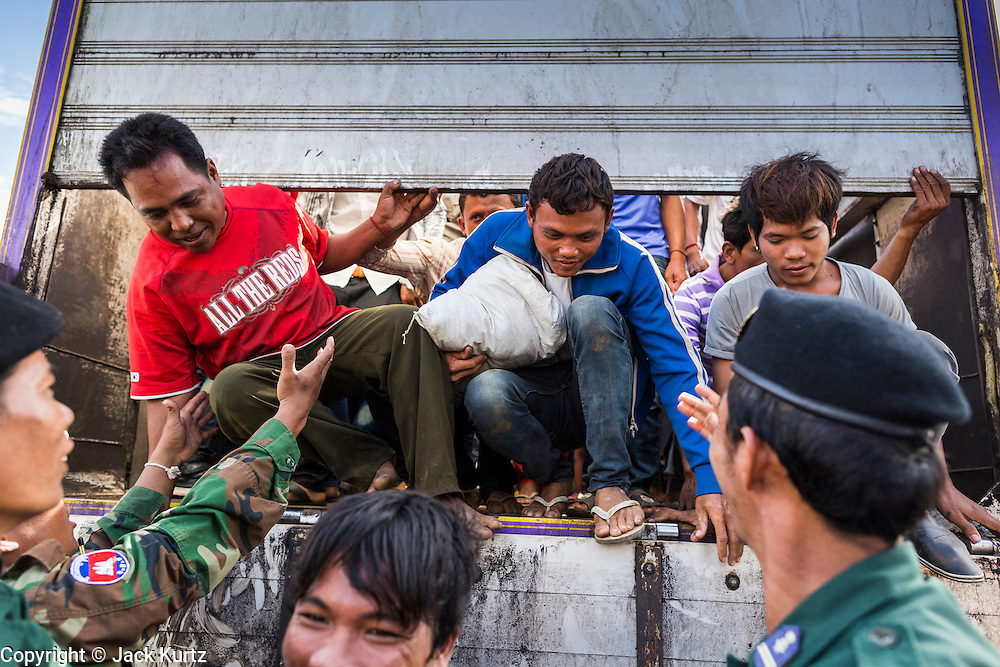 16 JUNE 2014 - POIPET, CAMBODIA: Cambodian migrants jump out of a dump truck that brought them back to Cambodia from Thailand. More than 150,000 Cambodian migrant workers and their families have left Thailand since June 12. The exodus started when rumors circulated in the Cambodian migrant community that the Thai junta was going to crack down on undocumented workers. About 40,000 Cambodians were expected to return to Cambodia today. The mass exodus has stressed resources on both sides of the Thai/Cambodian border. The Cambodian town of Poipet has been over run with returning migrants. On the Thai side, in Aranyaprathet, the bus and train station has been flooded with Cambodians taking all of their possessions back to Cambodia.  PHOTO BY JACK KURTZ