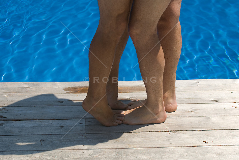 Detail of Two men's legs and feet together by a swimming pool