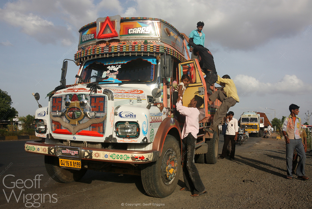 Hitch hikers disembark from Indian Tata 1613 truck on Gujarat highway. India