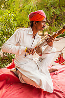 A man playing a traditional instrument called an erhu in Jodhpur, Rajasthan, India.