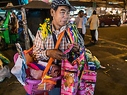 "21 DECEMBER 2015 - BANGKOK, THAILAND:  A vendor who who walks through the market selling aprons in Pak Khlong Talat, also called the Flower Market. The market has been a Bangkok landmark for more than 50 years and is the largest wholesale flower market in Bangkok. A recent renovation resulted in many stalls being closed to make room for chain restaurants to attract tourists. Now Bangkok city officials are threatening to evict sidewalk vendors who line the outside of the market. Evicting the sidewalk vendors is a part of a citywide effort to ""clean up"" Bangkok.      PHOTO BY JACK KURTZ"