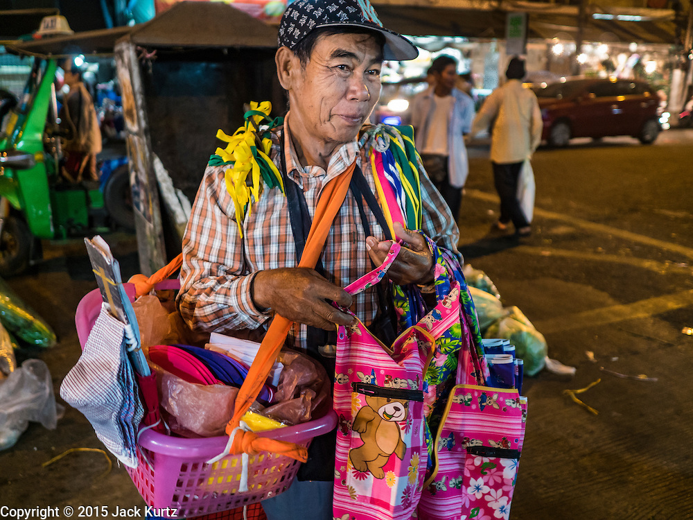 """21 DECEMBER 2015 - BANGKOK, THAILAND:  A vendor who who walks through the market selling aprons in Pak Khlong Talat, also called the Flower Market. The market has been a Bangkok landmark for more than 50 years and is the largest wholesale flower market in Bangkok. A recent renovation resulted in many stalls being closed to make room for chain restaurants to attract tourists. Now Bangkok city officials are threatening to evict sidewalk vendors who line the outside of the market. Evicting the sidewalk vendors is a part of a citywide effort to """"clean up"""" Bangkok.      PHOTO BY JACK KURTZ"""