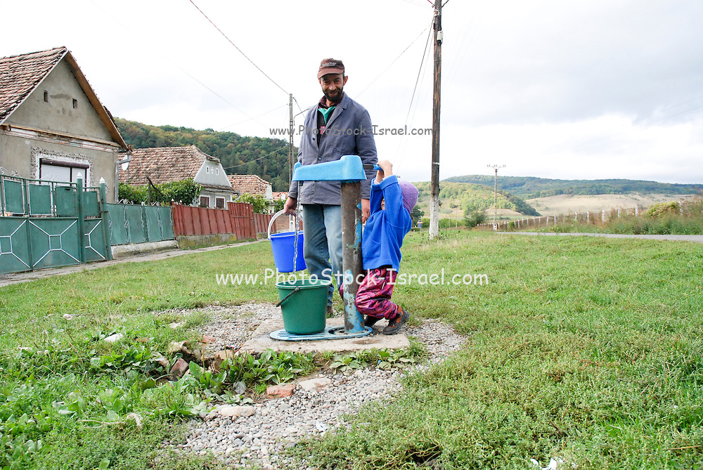 Romania, Local peasant pumps water from a public water well