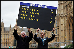 L to R Pete Waterman, record producer and songwriter, and Andrew Adonis, Labour politician who was Secretary of State for Transport between 2009-2010 hold up a High Speed Rail Arrivals card outside the House of commons in favour of the announcement  today that Phase one of high-speed rail line gets go-ahead, Tuesday January 10, 2012. Photo By Andrew Parsons/ i-Images