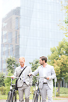 Businessmen with bicycles walking against office building