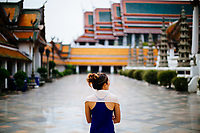 A woman walks through Wat Suthat in Bangkok, Thailand.