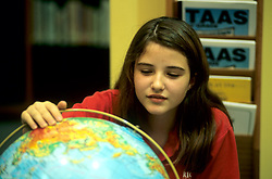 Stock photo of a young girl looking at a globe in a classroom