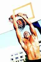 A physically fit man reverse dunking a basketball at an outdoor basketball court.