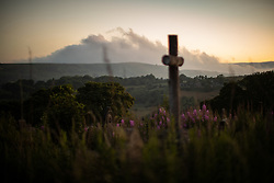 """© Licensed to London News Pictures . 28/06/2018 . Saddleworth , UK . View of smoke on hills across Saddleworth moor as viewed from Saddleworth Graveyard , where fire burned through dry grass in the late hours of Wednesday 27th June (yesterday) and had to be extinguished by firefighters . The army are being called in to support fire-fighters , who continue to work to contain large wildfires spreading across Saddleworth Moor and affecting people across Manchester and surrounding towns . Very high temperatures , winds and dry peat are hampering efforts to contain the fire , described as """" unprecedented """" by police and reported to be the largest in living memory . Photo credit: Joel Goodman/LNP"""