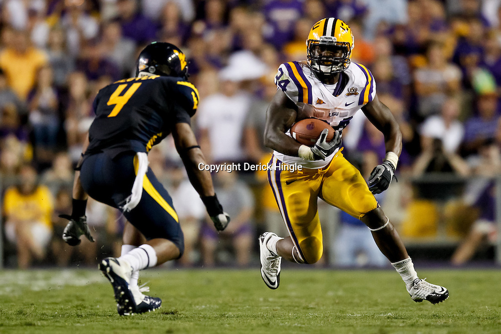 Sep 25, 2010; Baton Rouge, LA, USA; LSU Tigers running back Stevan Ridley (34) runs as West Virginia Mountaineers defensive back Sidney Glover (4) pursues the play during the second half at Tiger Stadium. LSU defeated West Virginia 20-14.  Mandatory Credit: Derick E. Hingle