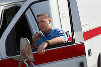 Paramiedic using CB radio, leaning on ambulance