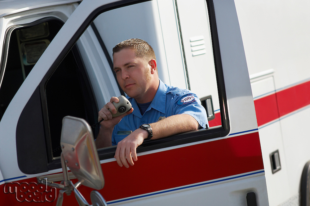 Paramiedic using CB radio, leaning on ambulance